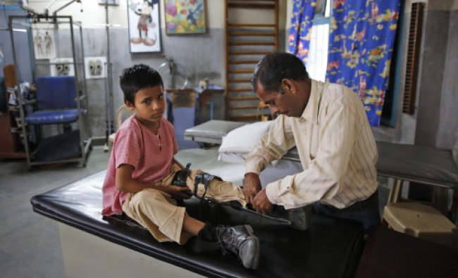 A man puts on an orthoses on his polio-affected boy Manish, 8, at a physical rehabilitation center..