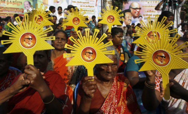 Supporters holds up Dravida Munnetra Kazhagam (DMK) party symbols and portraits of party chief...