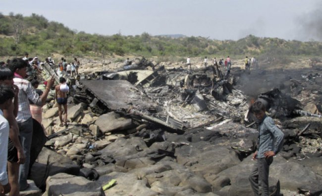 Onlookers stand next to the debris of a crashed U.S.-made C-130J Hercules aircraft of Indian Air...