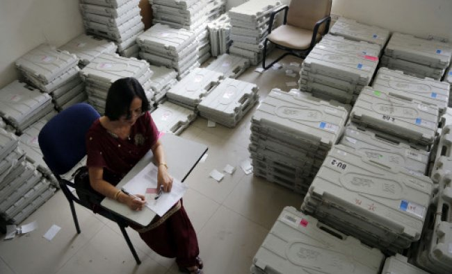 An Indian election officer writes on a strip of paper to stick on an Electronic Voting Machine...