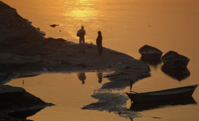 Devotees stand on the banks of river Ganges before taking a holy dip during the early morning...