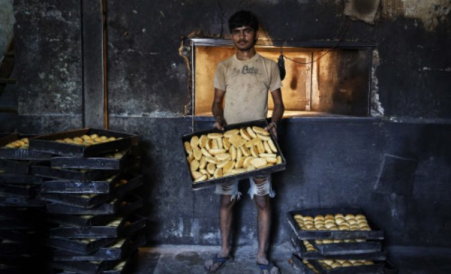 Sameer, a 20-year-old worker, poses inside a bakery at a slum in Mumbai...