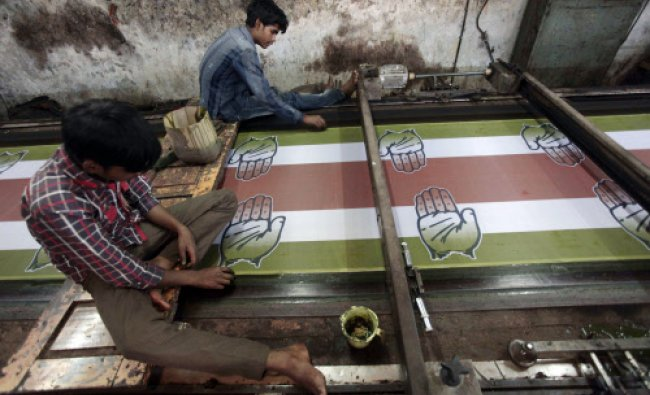 Workers run a printing machine to produce election campaign material for Indias ruling Congress...