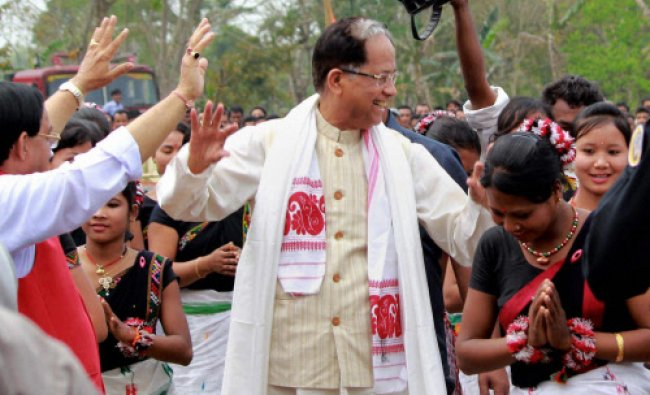 Assam Chief Minister Tarun Gogoi dances as he arrives to address an election campaign...