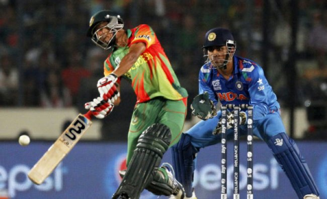 Bangladesh\'s Nasir Hossain plays a ball as India\'s captain and wicketkeeper M.S Dhoni...