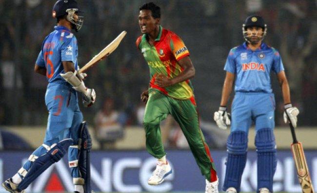 Shikhar Dhawan leaves the field as Bangladesh\'s Al-Amin Hossain (C) celebrates his dismissal...