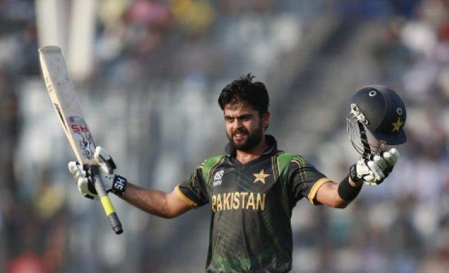 Pakistan batsman Ahmed Shehzad raises his bat and helmet to celebrate scoring a century...