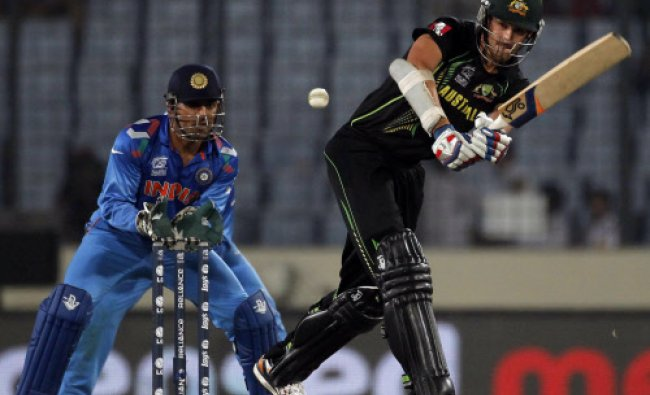 Australia\'s Mitchell Starc plays a ball as India\'s captain and wicketkeeper M.S Dhoni watches ...