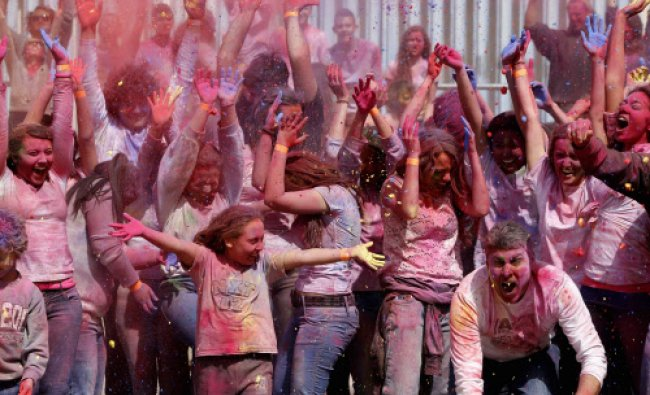 Participants dance and throw coloured powder during the Holi Festival of Colours organised ...