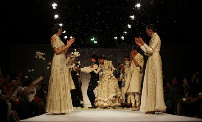 Audience shower flowers at designer Sahil Kochhar, center left, as models, displaying his ...