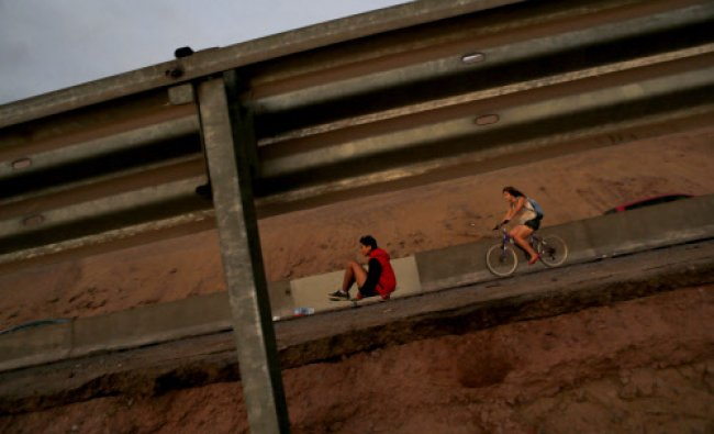 Residents cycle and skateboard along a damaged road to Alto Hospicio commune ...