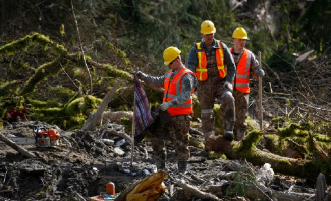 Members of the Washington State National Guard search through debris field for personal items ...