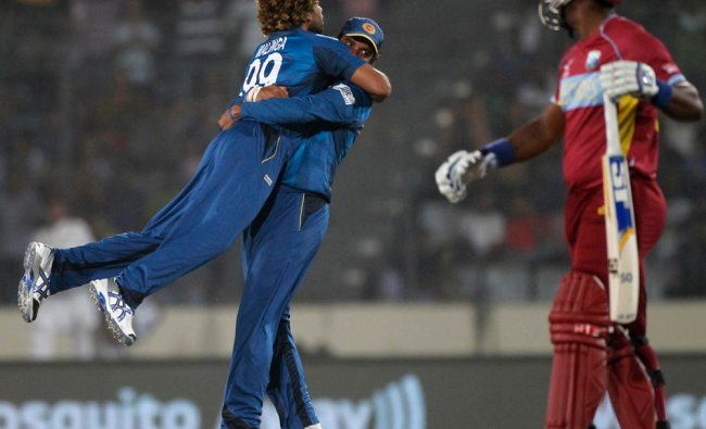 West Indies\' Smith leaves the field as Sri Lanka\'s Thirimanne congratulates bowler Malinga ...