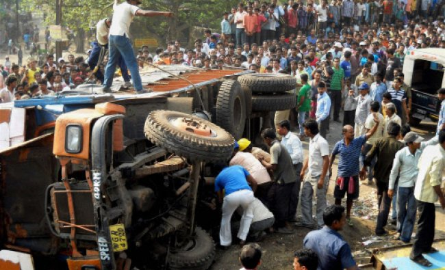 Local residents try to rescue people stuck after a truck overturned at Burdwan district in West...
