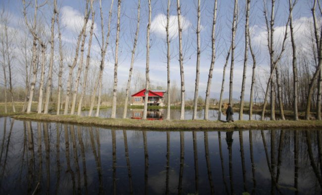 A Kashmiri man is reflected in a canal as he walks on the outskirts of Srinagar, AP Photo