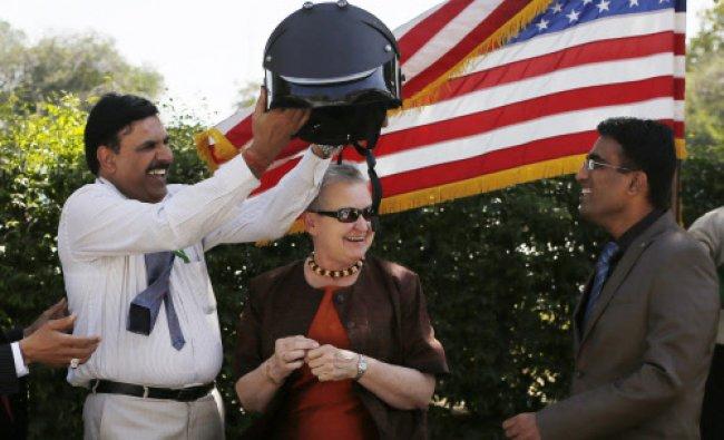 .S. Chuadhary, a senior official of Mumbai Police, holds a bomb-proof helmet as U.S. ambassador...