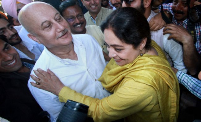 Bollywood actor Anupam Kher and his wife BJP candidate Kirron Kher hug each other during election...