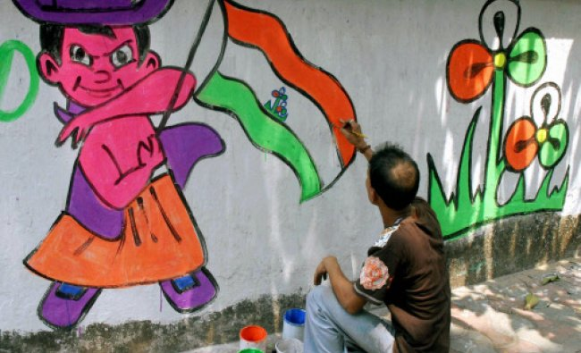 A Trinamool Congress worker makes a wall graffiti ahead of Lok Sabha election in Kolkata on ...