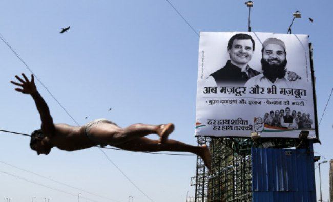 A boy dives into the Arabian Sea as India\'s ruling Congress party\'s election campaign banner...