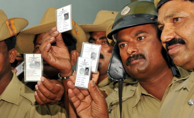 Karnataka State Reserve Police mens display their Election ID during Postal Voting in Mysore ...
