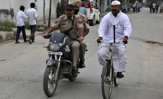 An independent candidate Shyam Lal Gandhi rides his bicycle next to his security personnel on...