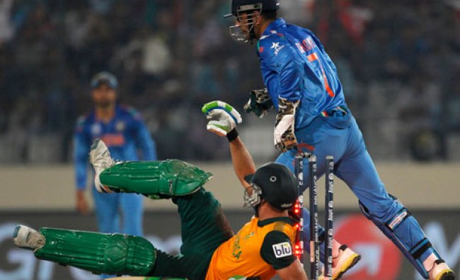 South Africa\'s captain Faf du Plessis falls on ground as M.S Dhoni (R) celebrates his dismissal...
