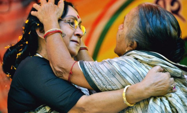 Actress and TMC candidate Sandhya Roy seek blessings from an elderly woman during her election...