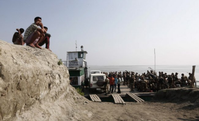 Boys sit on the banks of Brahmaputra river as Indian security personnel deployed on election duty...