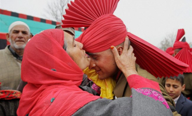 A mother kissing her son during his pipping ceremony after a passing out parade of army at Jammu...