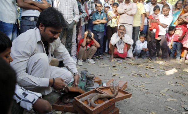 A crowd gathers to watch a snake charmer, AP Photo