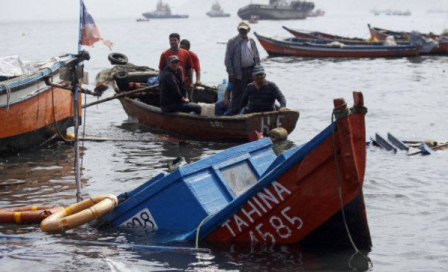 Fishermen look for boats to salvage damaged overnight in the port of Iquique, Chile. Chilean...
