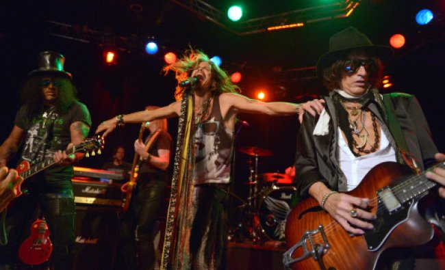 Slash, left, performs with Steven Tyler and Joe Perry, right, of Aerosmith at the Whisky A Go Go...