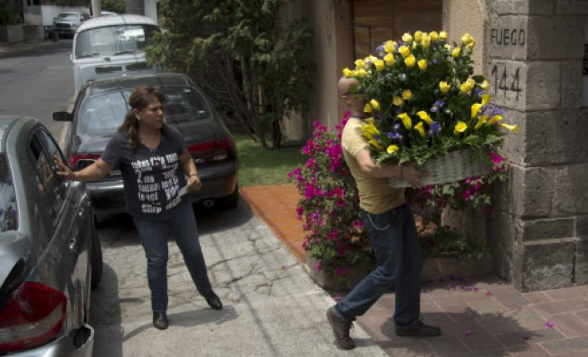 A man arrives with flowers to the home of Gabriel Garcia Marquez in Mexico City, Tuesday, April 8...