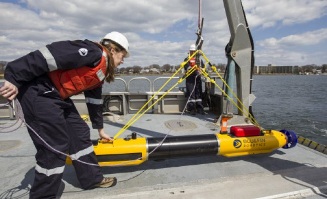 A submarine built by Bluefin Robotics is prepared by systems engineer Cheryl Mierzwa to be...