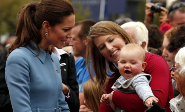 Catherine (L), Duchess of Cambridge, reacts as she meets a baby in the crowd after laying a...