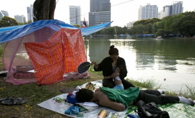 Anti-government protesters relax in the afternoon heat in Lumpini Park in downtown Bangkok...