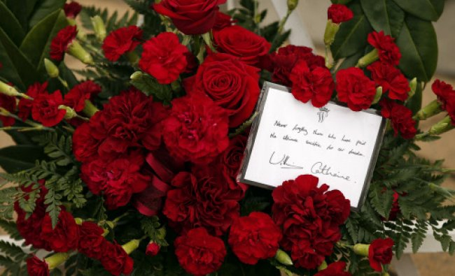 A card can be seen on the wreath that Britain\'s Prince William and his wife Catherine, Duchess of...