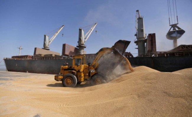 A dozer unloads wheat next to a ship at Mundra Port in Gujarat...