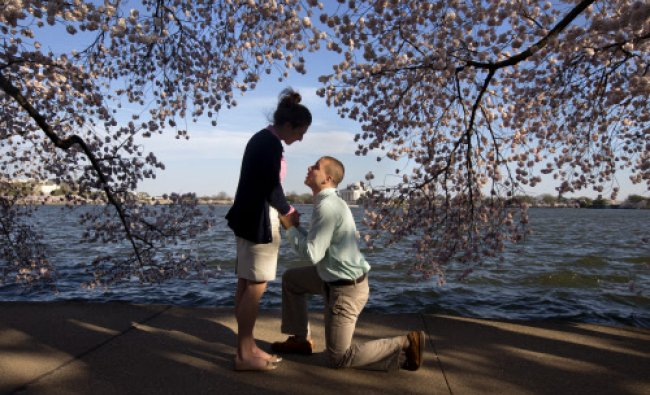 With the Jefferson Memorial in the background, Steven Paska, 26, right, of Arlington, Va., kneels...