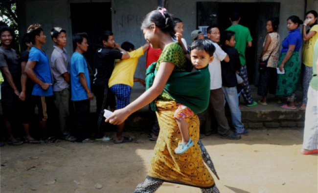 A woman carries her kid as people wait to cast their votes for Lok Sabha polls at a polling...