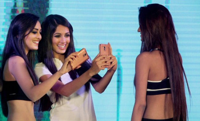 Models display the newly launched Samsung Galaxy S 5 smartphone during a fashion show in ...
