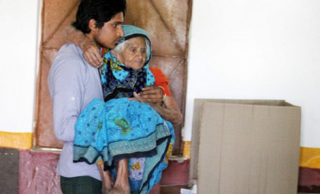 An elderly woam being carried at a polling station to cast her vote during the Lok Sabha Election...