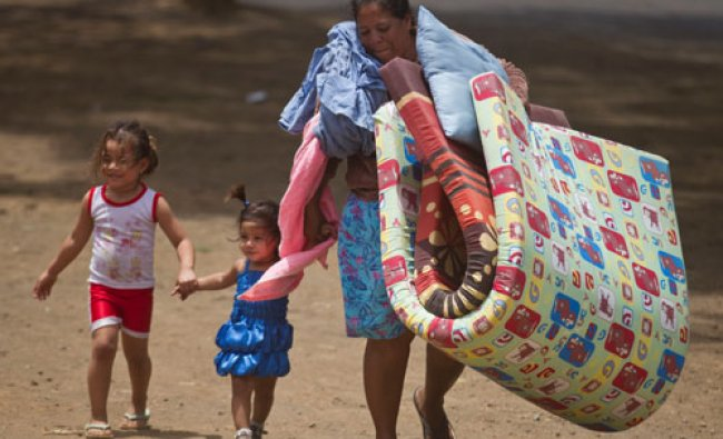 A woman carries mats to a shelter for people displaced by a 6.1-magnitude quake, in Managua...