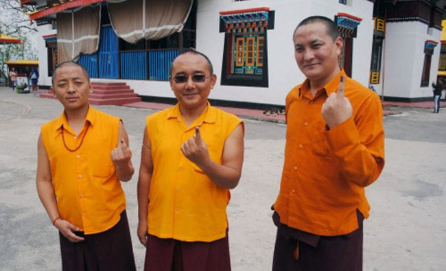Monks showing their ink marked fingers after casting votes for Lok sabha polls at Enchey ...