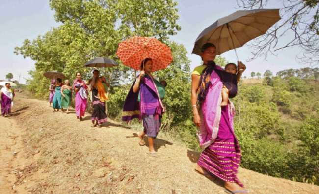 Women carrying their children walk back to their homes after casting their vote at a polling ...