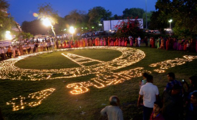 People light earthen lamps in a formation to create voting awareness in Bikaner. PTI Photo
