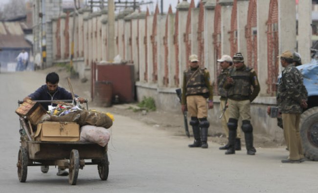 A Kashmiri sweeper pushes a cart filled with garbage past Indian Paramilitary soldiers during a...