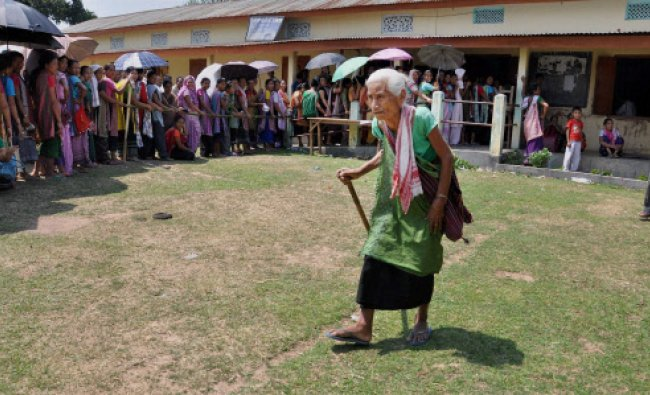 An old woman arrives as people wait in a queue to cast their votes for Lok Sabha polls at a ...
