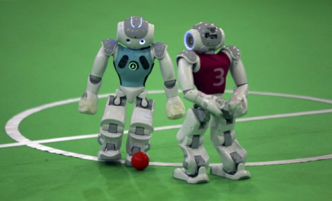 Humanoid robots play during a soccer match during the international robotics competition...