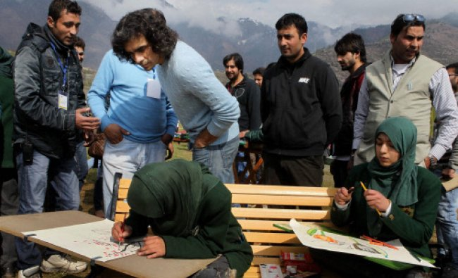 Film-maker Imtiyaz Ali watching a girl\'s drawing at a painting competition during the first...